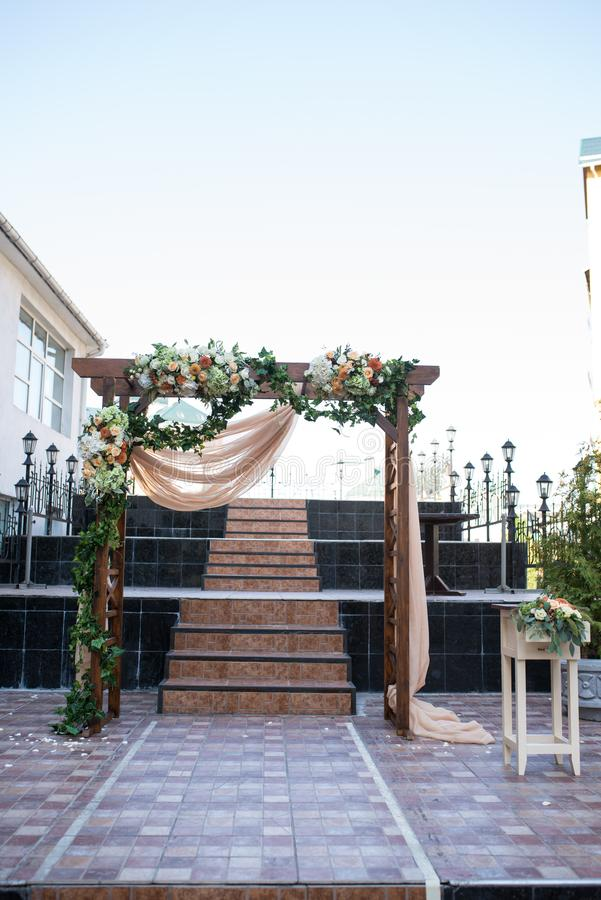 Rustic wedding arch. Wedding arch made of wooden square frame, beige cloth, white and orange flowers. Beautiful wedding ceremony o. Utdoors. wedding royalty free stock photography