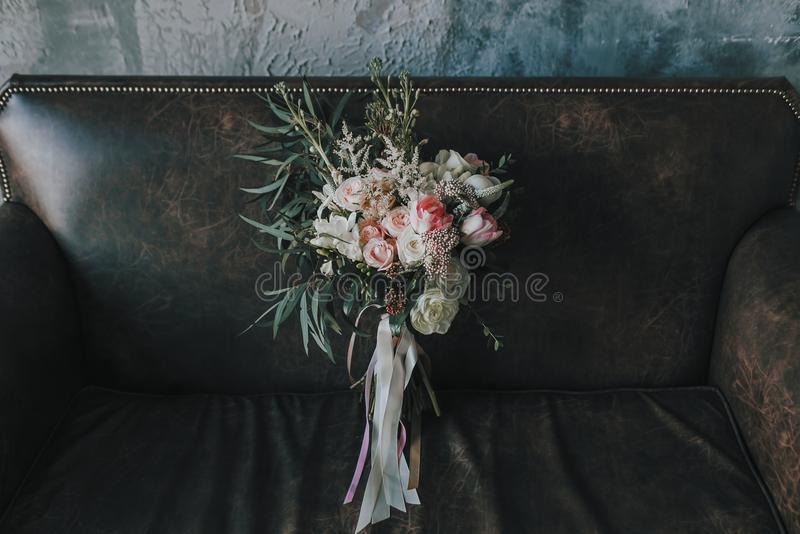 Rustic wedding bouquet with light roses and other flowers on a luxury brown sofa. Close-up. Central view. Indoors royalty free stock image