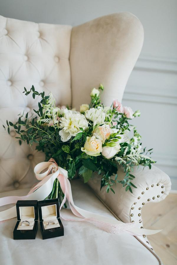 Rustic wedding bouquet and rings in the black box on a luxury sofa. Indoors. Artwork stock image