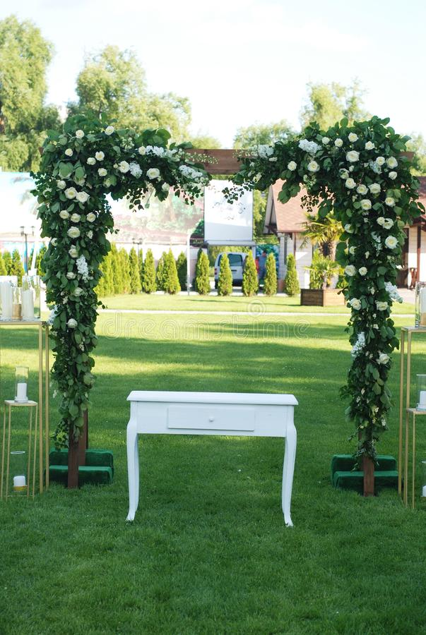 Rustic Wedding Ceremony Arch on the Open Area with Greem Grass. Wooden Arch with Flowers Arrangement. Rustic Wedding Ceremony Arch on the Open Area with Greem stock photo