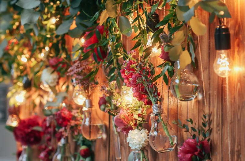 Rustic wedding photo zone. Hand made wedding decorations includes Photo Booth red flowers. Garlands and light bulbs royalty free stock photography