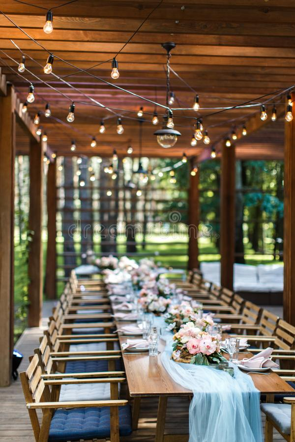 A rustic wedding table on the terrace of a restaurant in the forest stock photos