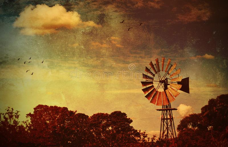 Grunge textured windmill at sunrise stock images