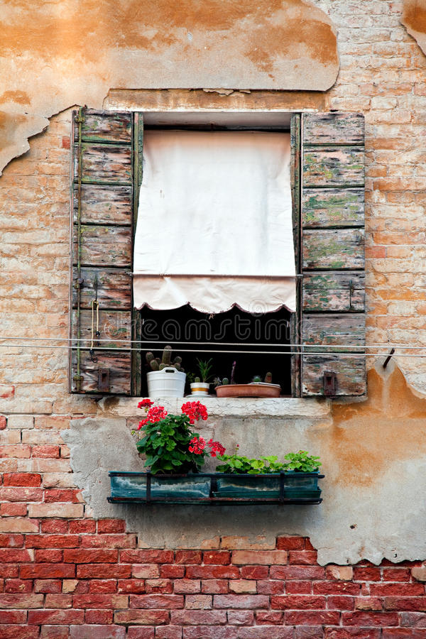 Rustic window with shutters in old venice house. With orange and red color wall royalty free stock photography