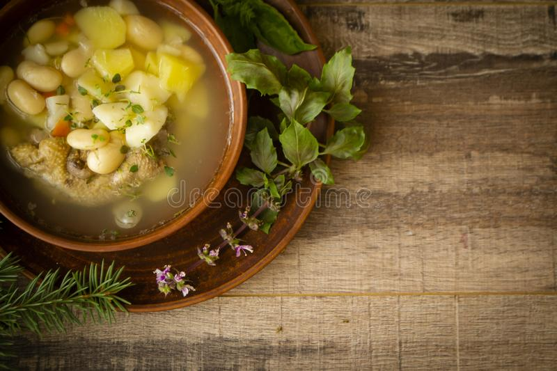 Rustic winter soup of russian cuisine, bowl of chicken soup with beans. Top view, copy space. Rustic winter soup of russian cuisine, bowl of chicken soup with stock image