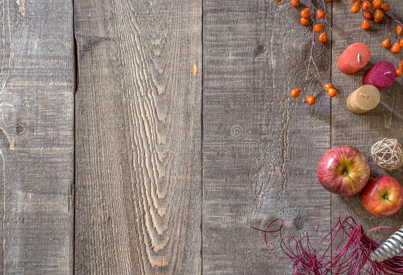 Rustic wood plank background with autumn candles, apples and berries along right side border. Space for text royalty free stock image