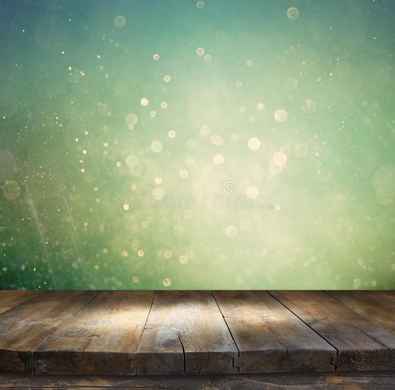 Rustic wood table in front of glitter silver, blue, and gold bokeh lights.  royalty free stock image