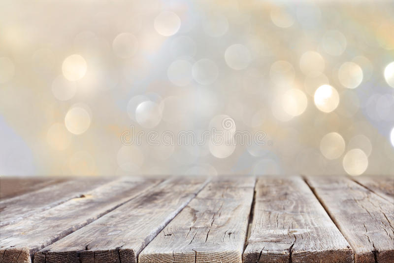 Rustic wood table in front of glitter silver and gold bright bokeh lights stock image