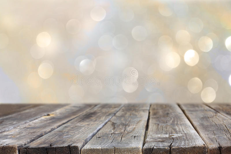 Rustic Wood Table In Front Of Glitter Silver And Gold