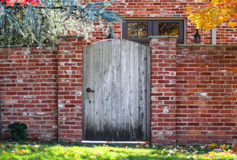 Rustic wooden arched garden fence in brick wall in autumn with colored leaves and brick house with colorful fall foliage reflected royalty free stock image