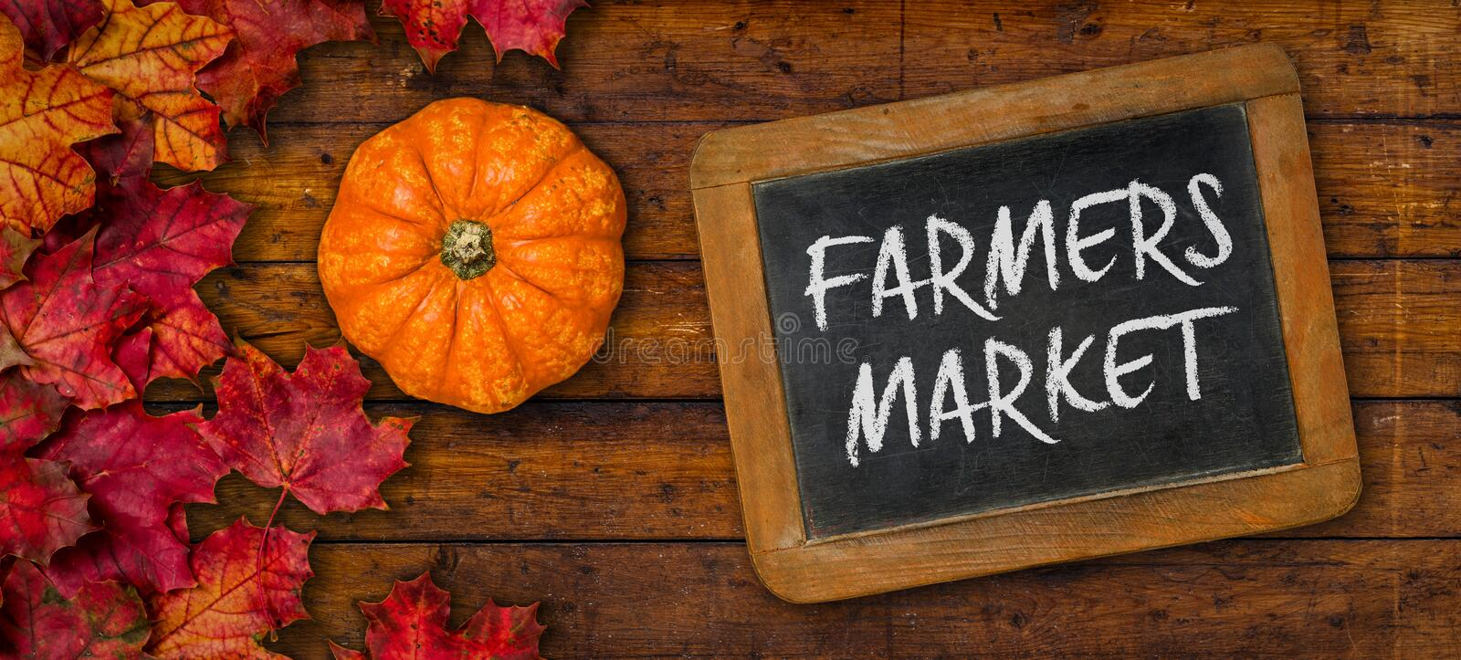 A rustic wooden background with autumn foliage - Farmers Market stock photo