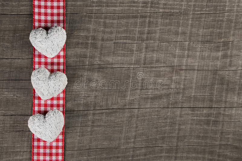 Rustic wooden background with red white checkered frame and three hearts. stock photos