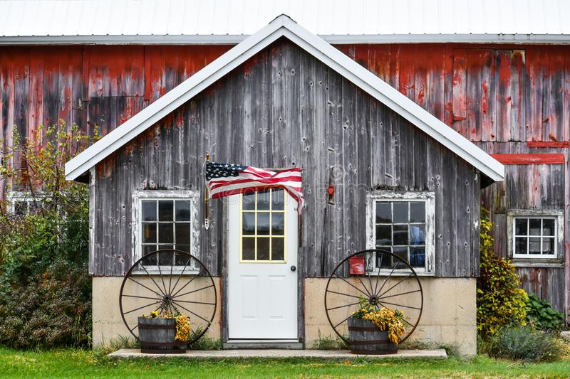 Rustic Wooden Barn with USA Flag Flying in Wind royalty free stock images
