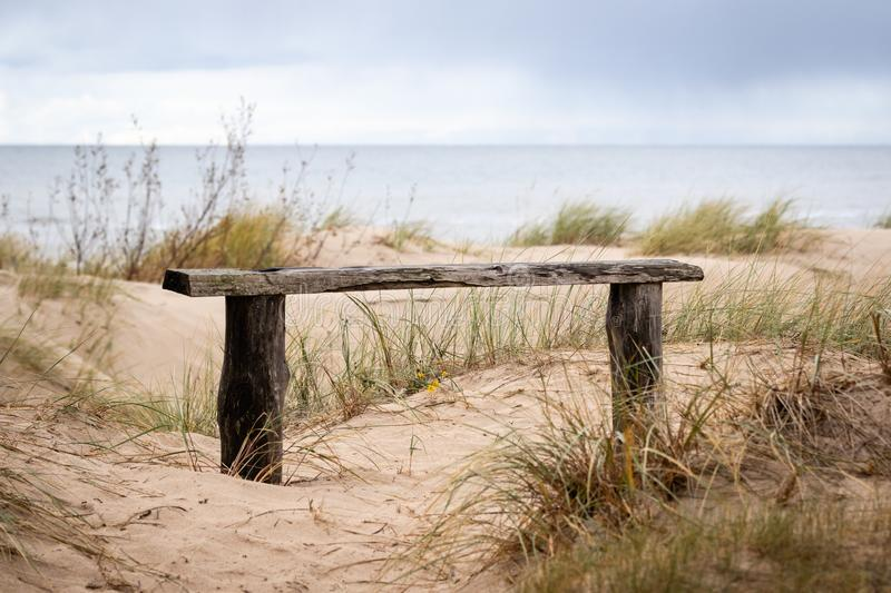 Rustic wooden bench in the dunes of baltic sea. Overcast day at the beach stock images