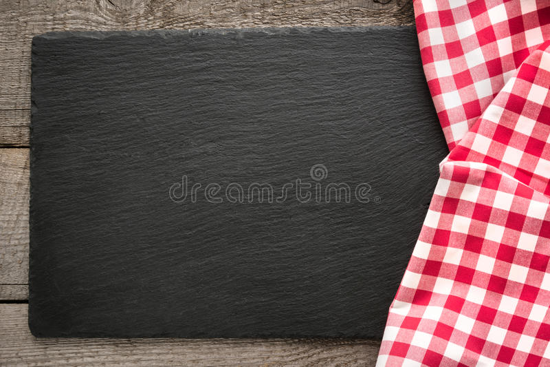 Rustic wooden boards, red checkered napkin and black slate dish with copy space for your menu or recipe. royalty free stock photos