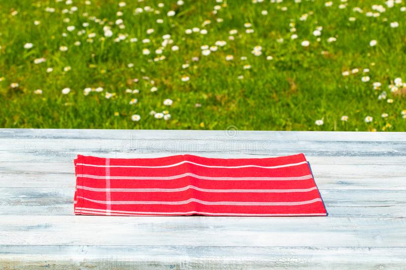 Rustic wooden bright table with beautiful spring meadow with daisies in background. Outdoor in morning. Space for products. Concept product presentation royalty free stock images