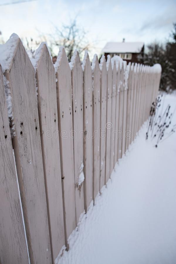Rustic wooden fence covered with snow on a blurred background of the house and garden, winter frosty evening royalty free stock image