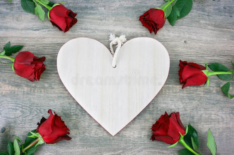 Rustic Wooden Heart and Red Roses Over Wooden Background for Valentine`s Day Holiday stock image