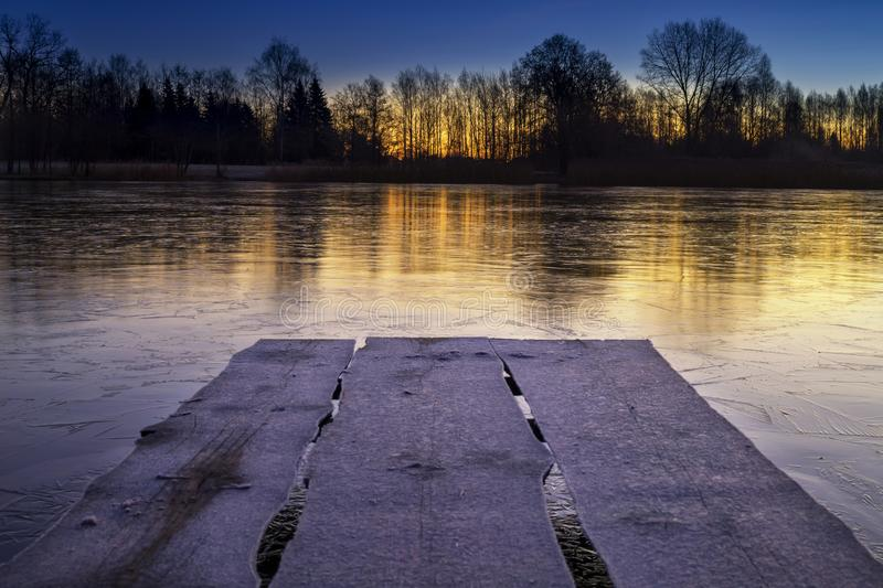 Rustic wooden jetty on a frozen lake at sunset royalty free stock image