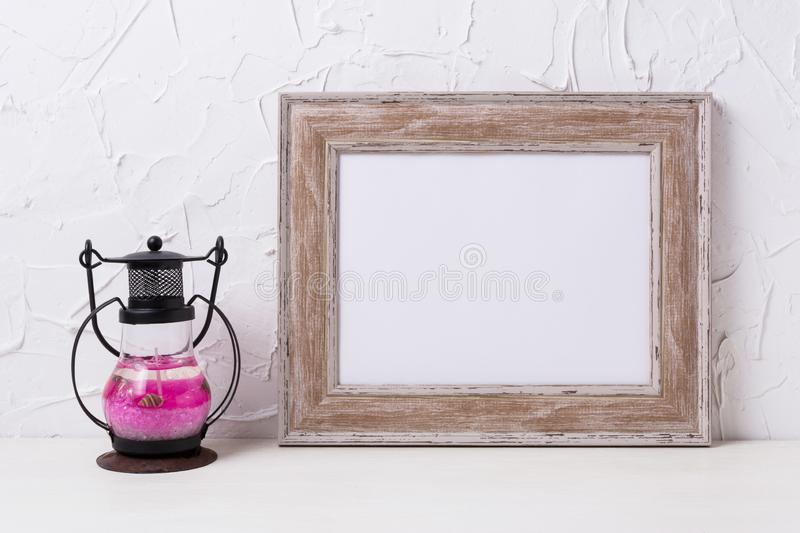 Rustic wooden landscape frame mockup with metal candle lantern. Rustic wooden landscape frame mockup with black pink metal candle lantern. Empty frame mock up royalty free stock photo