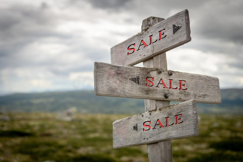 Rustic and wooden Sale signpost outdoors in Nature. royalty free stock photography