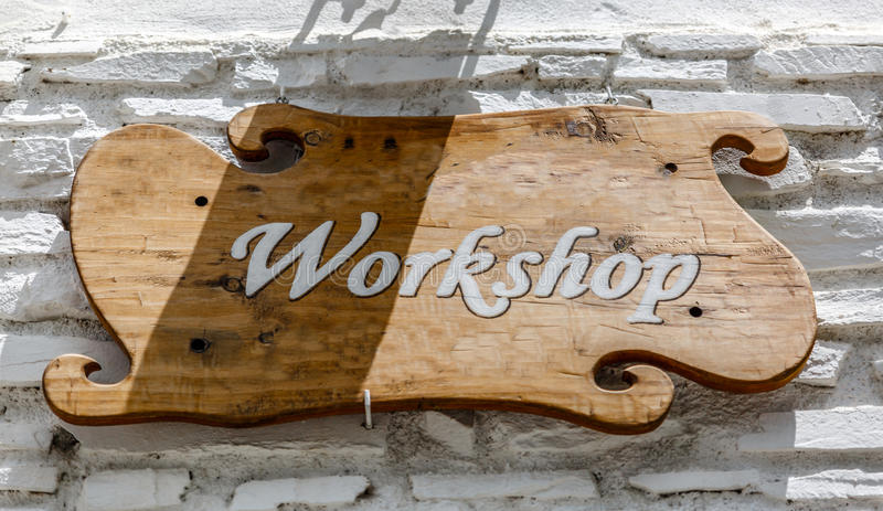 Rustic wooden signboard with the word workshop on a white wall stock image