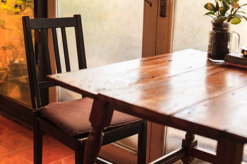 Rustic wooden table and chairs with warm natural light setting illuminated through door glass window. Indoor decoration, interior. Design, architecture, house royalty free stock images