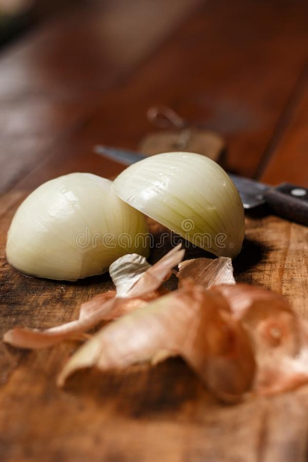 Rustic wooden table with a cutting board above. Knife cut in background onion cut in half as subject. Detail of onion peels in the royalty free stock images