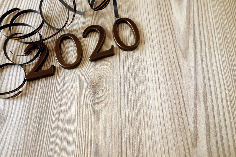 Rustic wooden table with digits and ribbons, Happy New Year 2020 background stock photo