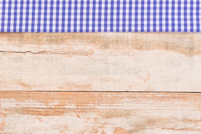 Oktoberfest background with blue white rustic fabric border on old wood. Rustic wooden table surface with blue checkered cloth, top view, background for royalty free stock image
