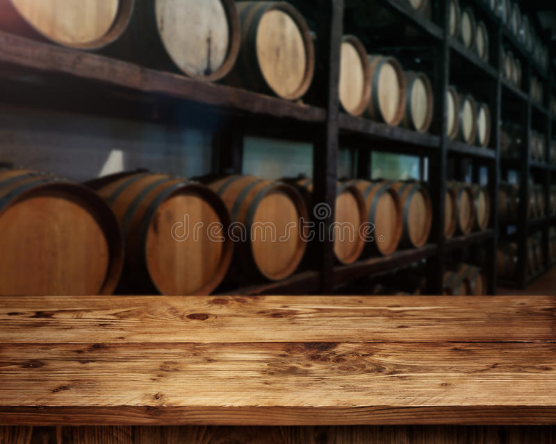 Rustic wooden table in a wine cellar. Rustic wooden table in front of wine barrels royalty free stock photography