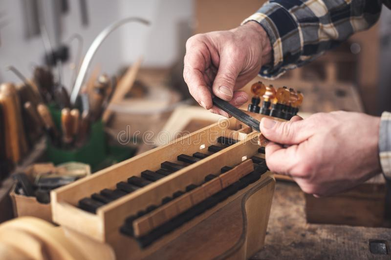 Instrument maker holding a key of a Hurdy Gurdy in his hands royalty free stock photography