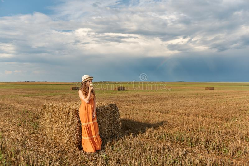 Rustic young woman in an orange sarafan and hat stands near a haystack and eats an apple with a background of a storm cloud and a royalty free stock photo