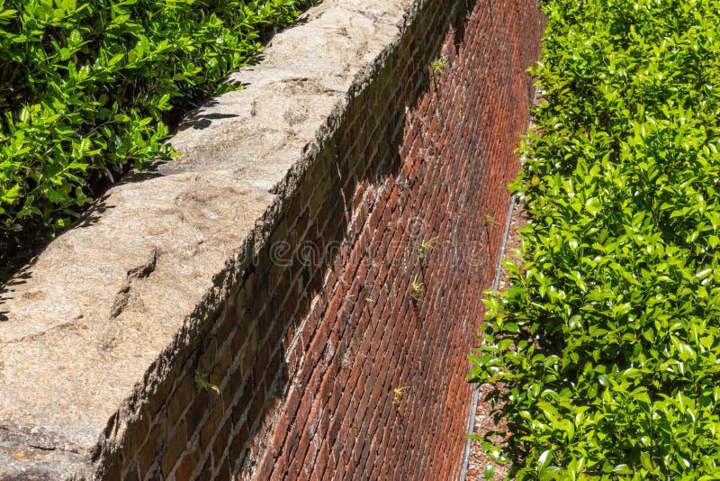 Rusticatedsteen GLB op een rode baksteen behoudende muur, overvloedig groen royalty-vrije stock foto's