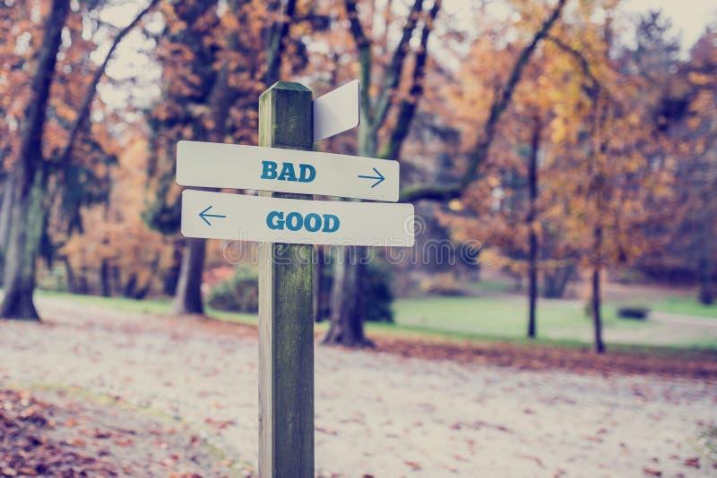 Rustiek houten teken in een de herfstpark met de Slechte woorden - Goed royalty-vrije stock foto