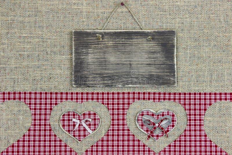 Rustiek houten teken met rode plaidgrens met hartknipsels op juteachtergrond stock fotografie