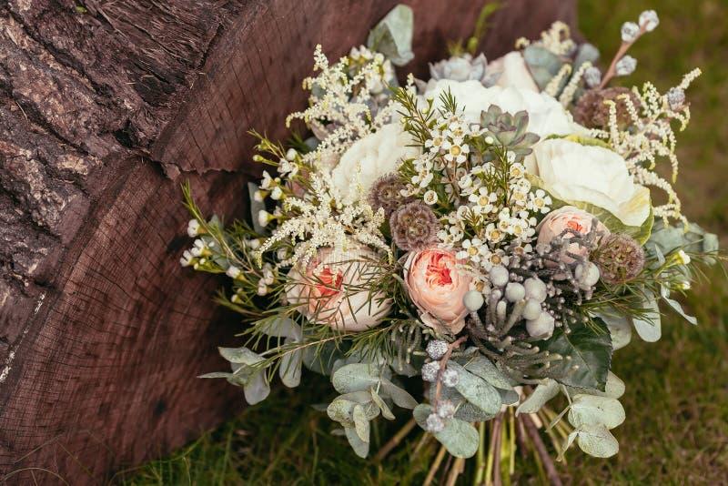Rustiek huwelijksboeket met rozen en succulents op groen gras royalty-vrije stock afbeelding