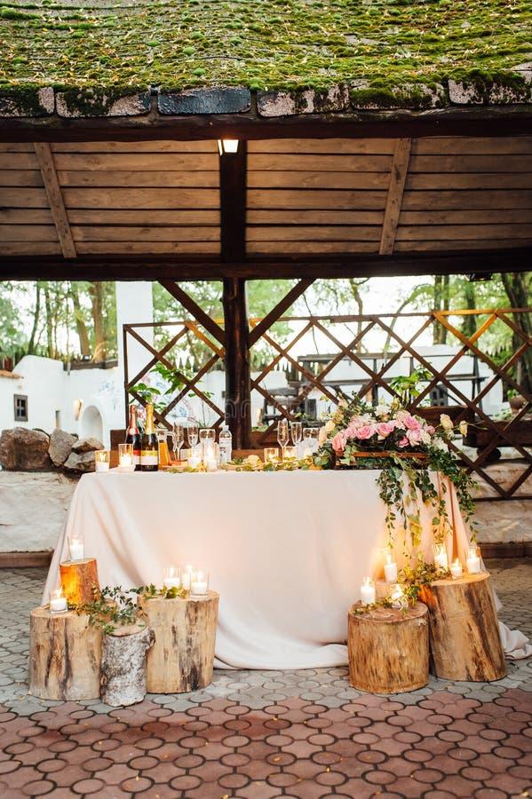 Rustiek huwelijksdecor op een houtachtergrond Hoofdlijst die voor bruid en bruidegomjonggehuwden plaatsen stock fotografie