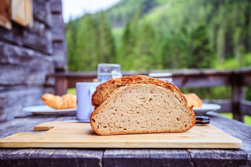 Rustiek ontbijt op een alpiene hut: verse kernachtige brood en melk in glasfles, in openlucht stock afbeelding