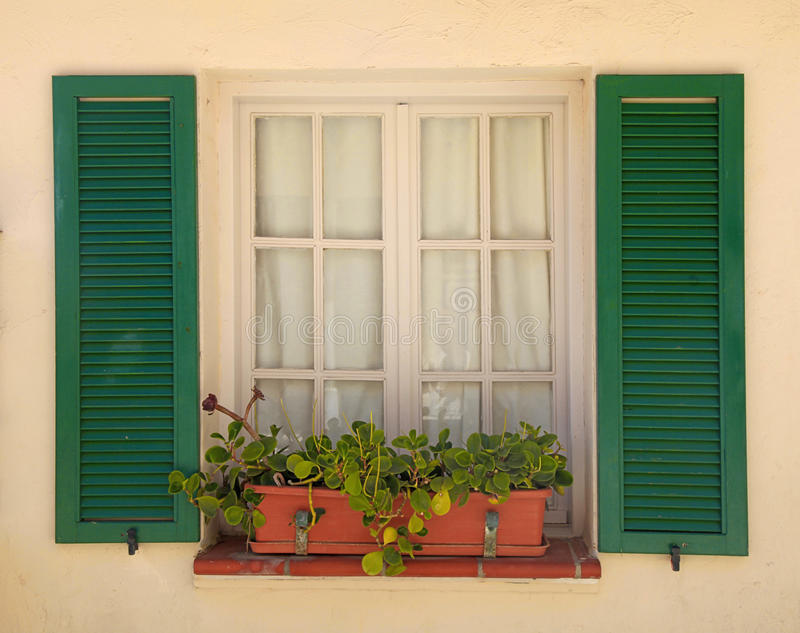 Rustiek venster met oude groene blinden en bloempot stock foto's
