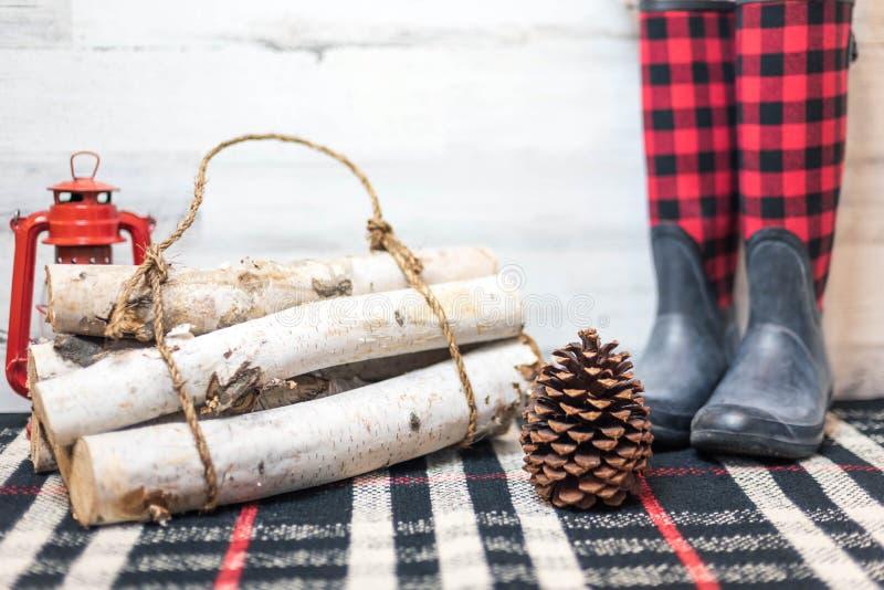 Rustieke de winterachtergrond met laarzen, logboeken en pinecone royalty-vrije stock afbeeldingen