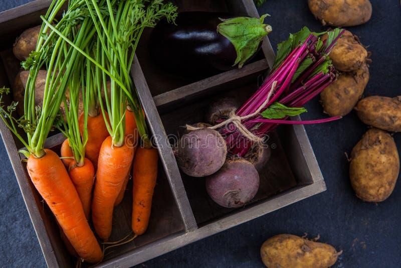 Rustieke doos met verse wortelen, bieten, aubergine en aardappels stock afbeeldingen