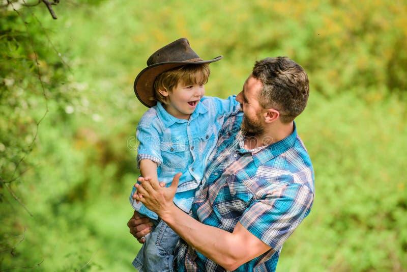 Rustieke familie Groeiende leuke cowboy Kleine helper in tuin Weinig jongen en vader op aardachtergrond Geest van stock foto