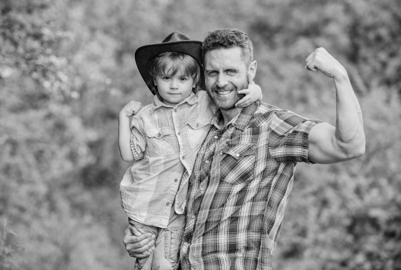 Rustieke familie Groeiende leuke cowboy Kleine helper in tuin Weinig jongen en vader op aardachtergrond Geest van royalty-vrije stock foto's