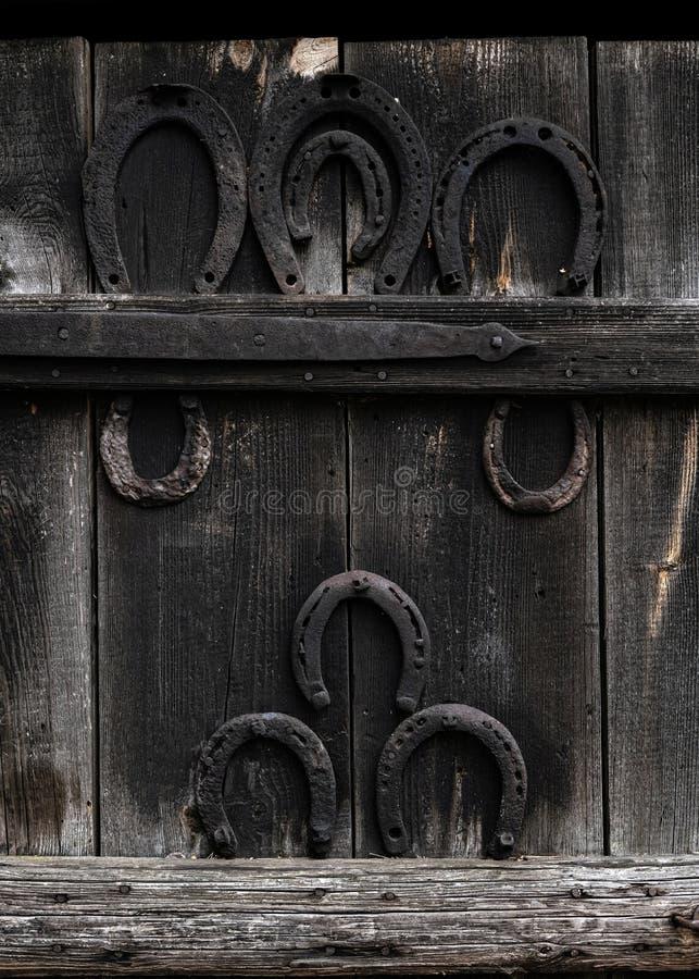 Rustieke hoef op uitstekende houten achtergrond Het oude paardschoen hangen op houten deur in het dorp - symbool van geluk stock afbeeldingen