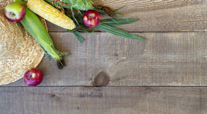 Rustieke houten de herfstachtergrond met strohoed, verse appelen en c royalty-vrije stock foto's