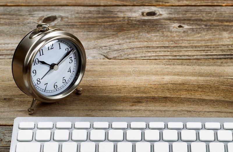 Rustieke houten Desktop met retro klok en toetsenbord stock fotografie