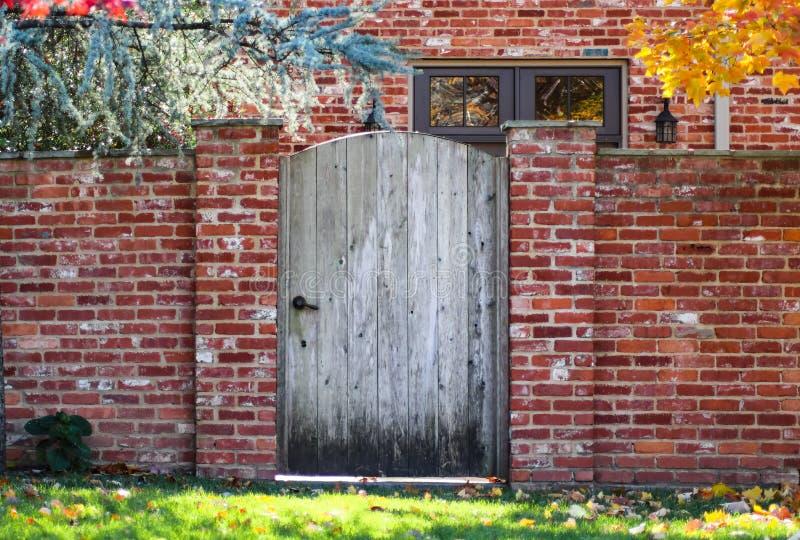 Rustieke houten overspannen tuinomheining in bakstenen muur in de herfst met gekleurd bladeren en baksteenhuis met kleurrijk weer royalty-vrije stock afbeelding
