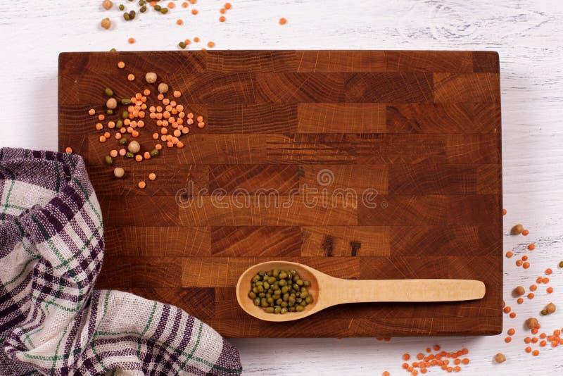 Rustieke houten raad, geruite servet en linzenzaden met cop stock afbeelding