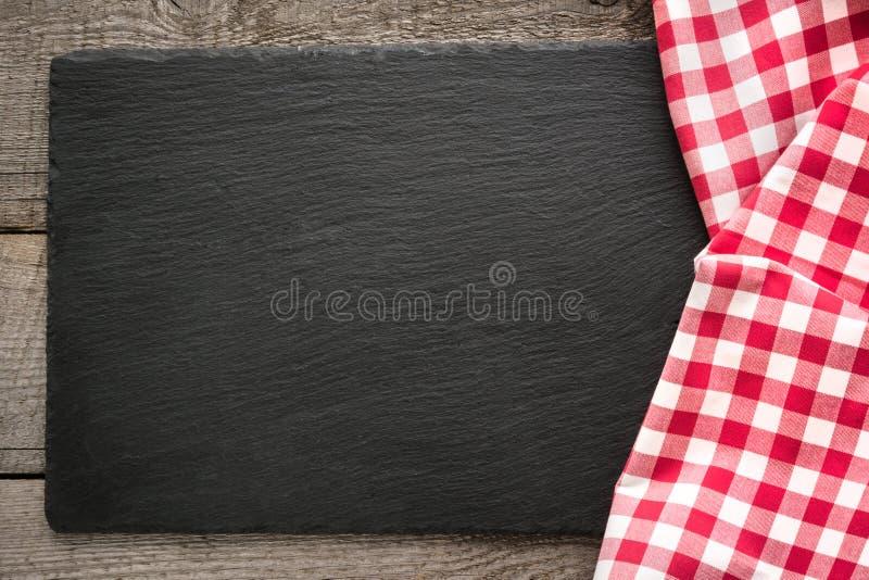 Rustieke houten raad, rood geruit servet en zwarte leischotel met exemplaarruimte voor uw menu of recept royalty-vrije stock foto's